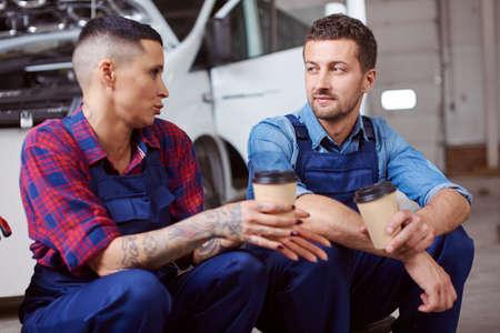 Two automechanics drink coffee at their lunch break. Foto de archivo