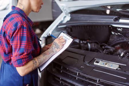 Automechanic maakt een lijst met problemen die gecontroleerd moeten worden.