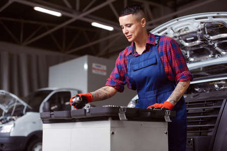 Car repair process with a woman in the middle of it.