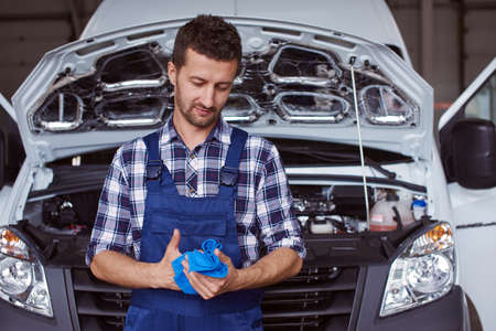 Automechanic wipes dirt off his hands with blue cloth.