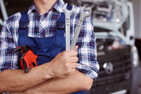 Man in car repair uniform stands near the broken truck. Foto de archivo
