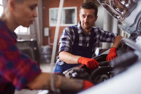 Automechanic teaches his colleague how to clean the engine. Foto de archivo