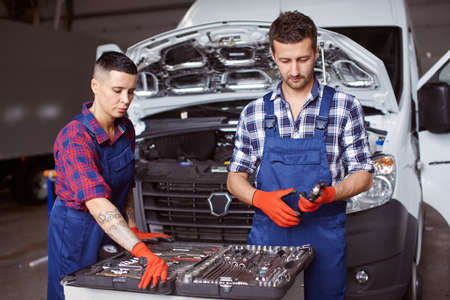 Two people working at the car repair workshop together.