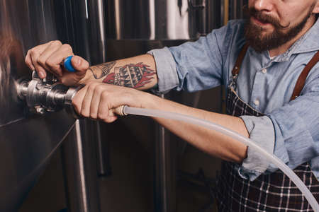 Bartender uses pipe to remove what is left in the big barrel.