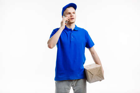 Mailman talks on the phone about the parcel he is about to deliver.