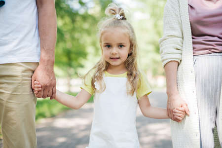 Portrait of a girl walking in the park with her parents. Stock Photo - 137171238