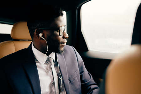 Man in headphones sits in the car and looks out of the window.