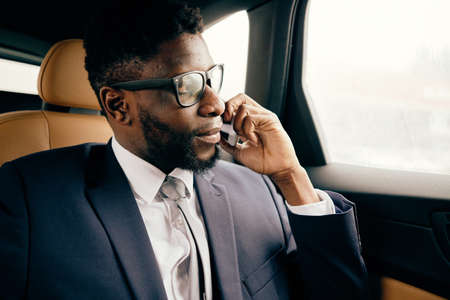 Businessman sits in the car and has conversation on the phone.