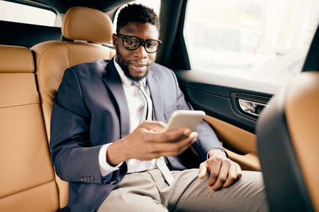 Businessman in a suit sits in a car back seat using his phone. Zdjęcie Seryjne
