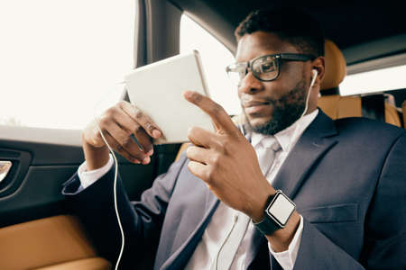 Man scrolling through the tablet screen during car ride.