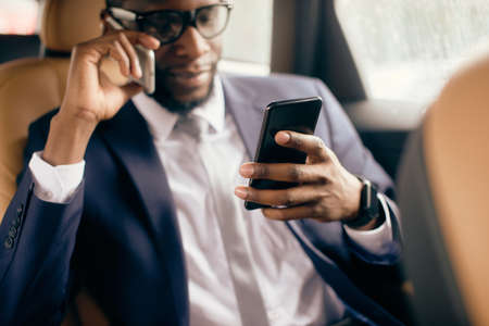 Man in a suit on the back car seat looking at the phone screen he holds. Zdjęcie Seryjne