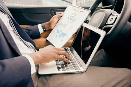Man works in his car with laptop and notepad depicting work related blueprints in front of him.