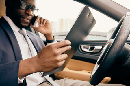 Businessman in a car holds a notepad and speaks on the phone.