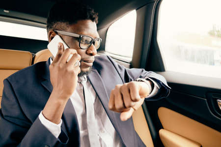 Businessman in car checks time on his watch to make sure he is going to be on a meeting on time. Фото со стока
