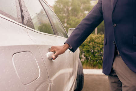 Close up of a man opening white car back door on a rainy day.