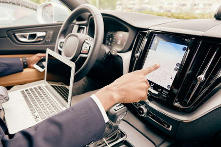 Close up of a driver using different devices he has in car.