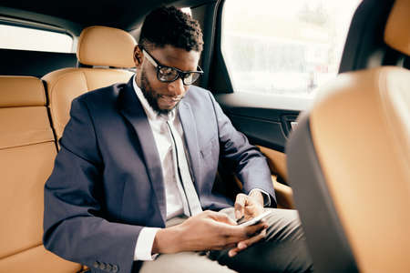 Man in a handsome suit on the back car seat uses his smartphone.