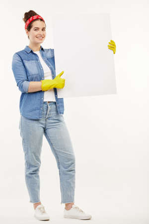 Pretty woman in work-wear holds a big white paper at the camera. Standard-Bild