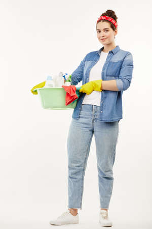 Pretty woman using several cleaning objects at the camera. Standard-Bild