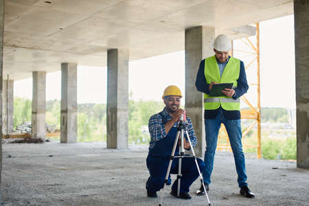 Two engineers on the construction use working equipment. Standard-Bild
