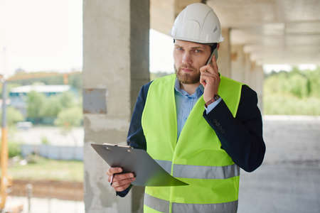 An engineer in a helmet talks on the phone and holds a notepad in a close-up.