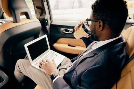 Man drinking coffee while working at the laptop on his way to airport.
