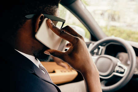 Close up of a driver talking on the phone he holds by his ear.