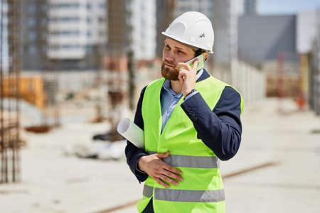 An engineer in a helmet talks on the phone.