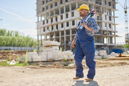 An engineer on the construction point holds work related equipment.