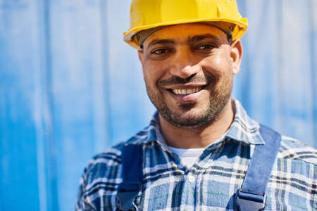 Smiling engineer in yellow construction helmet looks at the camera. Standard-Bild