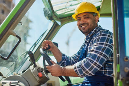 An engineer in uniform drives a green tractor.