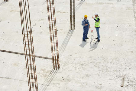 Two engineers in uniforms discuss work related questions together shot from above.