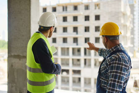 Two engineers in uniforms discuss work related questions together with the construction on the background.