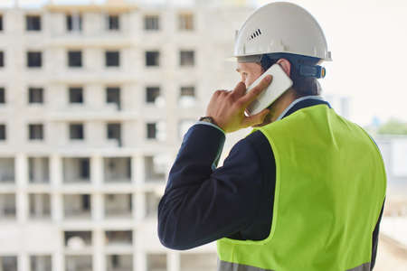 An engineer in a helmet and green safety vest talks on the phone.