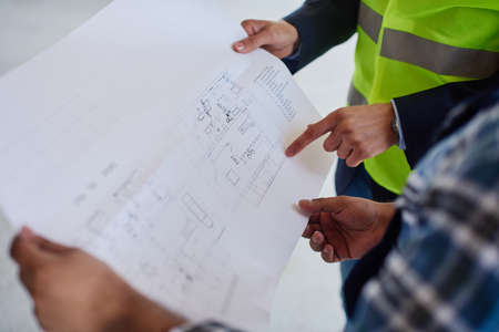 Close-up of a blueprint which two engineers examine.