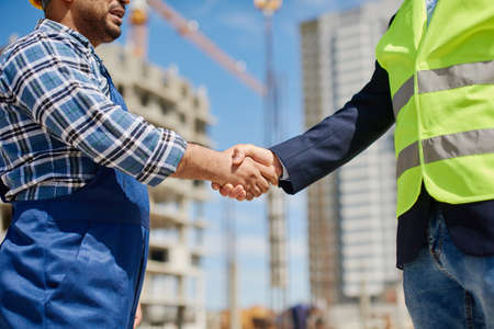 Two male engineers shake each others hands friendly.