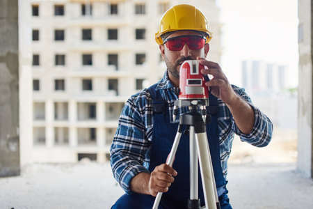 An engineers uses measuring equipment at his work place.
