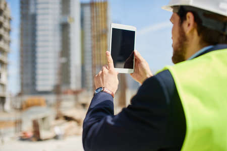 An engineer works on his tablet at the construction spot.