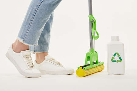 Close up of a woman in jeans and white sneakers with a green mop. Standard-Bild