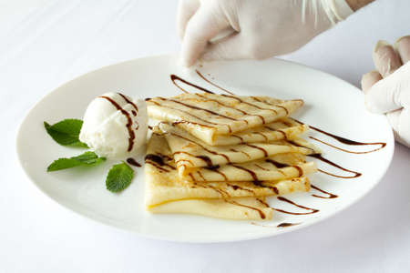 neatness: Serving dishes. Cook dish gloves cleans. Ice cream with pancakes on a white plate on a white background Stock Photo