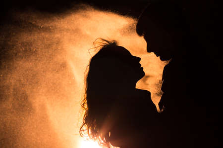 love: Loving couple silhouette. The wind carries sand. Stock Photo