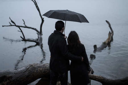 cloudy day: Couple stand back under an umbrella near the river Stock Photo