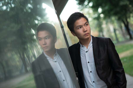 mirroring: Portrait of chinese elegant businessman near mirroring building