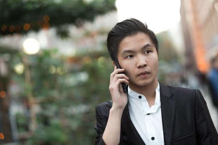 purposeful: Chinese elegant purposeful businessman in avenue speak by phone Stock Photo