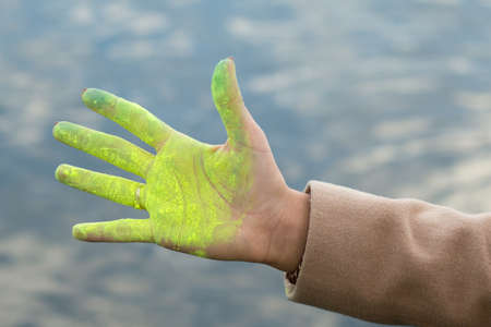 hand colored: Womans hand colored by bright yellow paint. River background. Stock Photo