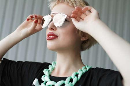 trash the dress: Closeup girl portrait. Woman holding sunglasses. Profiled sheeting wall background. The strange urban fashion photography