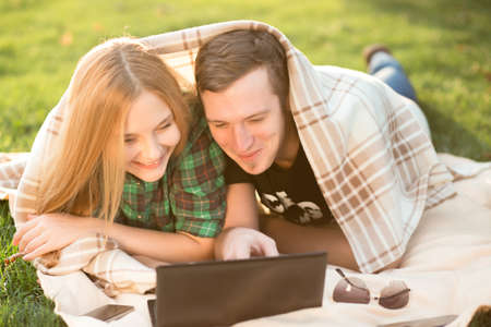 netbook: Young couple lying in the grass with a netbook