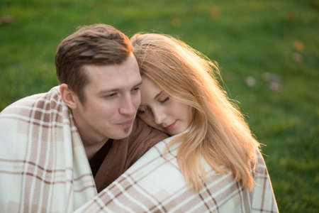Tenderness of a young couple in the park. They are under covers.