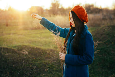 strew: Girl stands alone in the field and strew spikelets Stock Photo