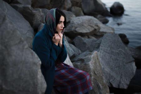 Meisje zit alleen in de rotsen aan de oever van de rivier en zijn eenzaam Stockfoto